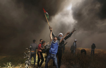 Palestinian demonstrators shout during clashes with Israeli troops at a protest at the Israel-Gaza border east of Gaza City