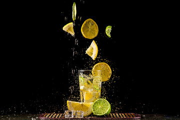 Levitating slices of lemon and lime, a splash of water.