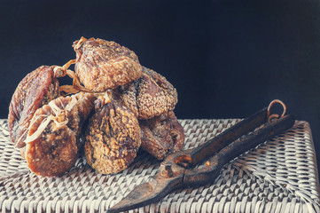 Dried sweet figs on the beam lies on a wicker basket with old garden scissors. Copy spase