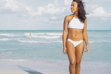 Beautiful shaped African-American woman in white swimwear posing on shoreline and looking away on background of ocean.