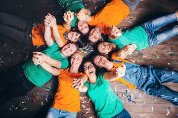 Happy friends lying together in circle looking at camera, keeping hands near mouth and smiling while lying on wooden floor.. Concepts about friendship,lifestyle,unity,business and teamwork.