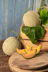 Close up cantaloupe melons in wooden box on wooden table