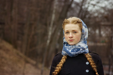 Portrait of a beautiful, young, red-haired girl with freckles in the park