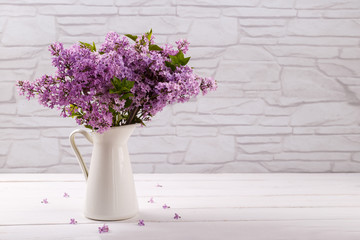 Bouquet of spring ,purple lilac flowers in a pitcher on white vintage wooden table, copy space