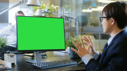 In the Office Businessman Makes Video Call on Personal Computer with Mock-up Green Screen. He Talks with Recipient and Actively Gesticulates, Expressing Surprise.