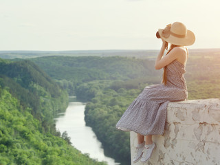 Girl sits on hill and takes pictures. Background of forest and river on background