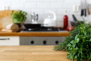 Fresh parsley and dill on wood counter with space for text. Out of focus home kitchen background.