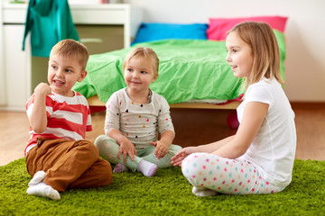 childhood, leisure and family concept - group of happy kids sitting on floor at home