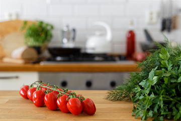 Grape tomatoes on vine on wood counter next to fresh herbs. Out of focus home kitchen background.