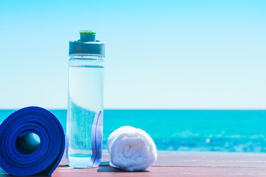Rolled Yoga Mat Bottle with Water White Towel on Beach with Turquoise Sea Blue Sky in Background. Sunlight. Relaxation Summer Meditation Fitness Wellbeing Mindful Living Concept. Copy Space