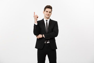 Business Concept: Handsome businessman with a finger pointed up isolated over white background
