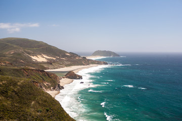 Green Rolling Hills and Waves Breaking on a Rough California Beach