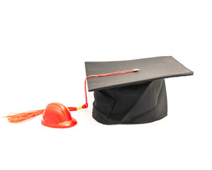 Studio shot of black graduation cap with red squeezable hard hat stress ball isolated on white. Construction education degree achievement and career concept. Clipping path, copy space