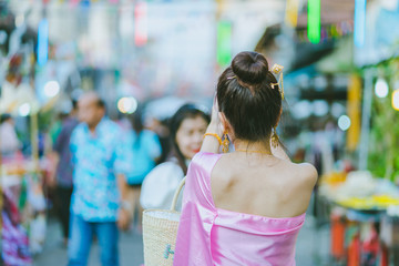 Young woman dressed in Thai costume take a photo.
