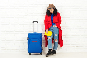 Young adorable woman in hat with suitcase ready for traveling.