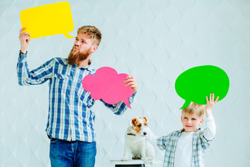 Portrait of beard man, cute preschooler boy in casual clothes with Jack russell terrier dog holding speech colorful bubbles, looking at camera and smiling, on a white background.