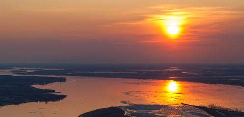 Beautiful sundown on the calm plain river, top view