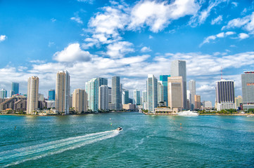 Aerial view of Miami skyscrapers with blue cloudy sky,white boat sailing next to Miami downtown