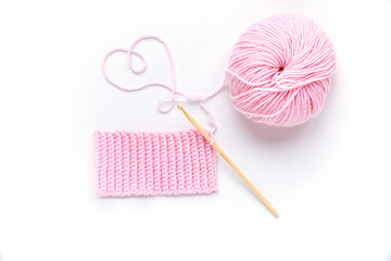 Pink ball of yarn with wooden crochet hook.