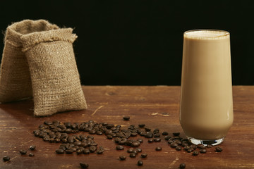 Coffee in glass with milk and cream with coffee beans.Horizontal  Black background. Front view. Copy space