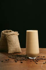 Coffee in glass with milk and cream with coffee bean, Black background and Copy space