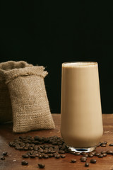 Coffee in glass with milk and cream with coffee beans.Vertical Black background. Copy space