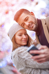 A beautiful young couple taking a selfie on the street with christmas lights in the background.