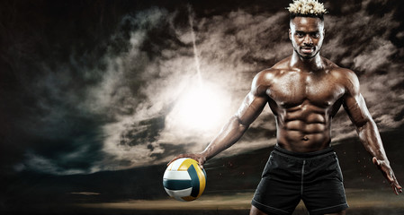 Portrait of afro-american sportsman, beach volleyball player with a ball over sunset. Fit young man in sportswear holding ball.
