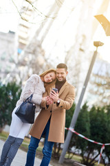 A beautiful young couple taking a selfie on the street with christmas trees in the background.