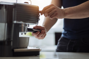 A man in the office prepares espresso for a coffee maker