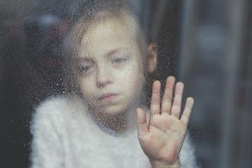 fillette triste à une fenêtre sous la pluie