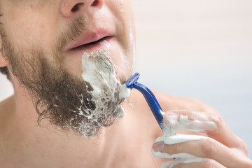 The guy shaves his beard, close-up