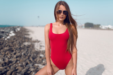Beautiful girl in red bathing suit lifeguard on white beach