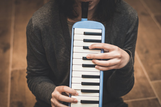 Someone is playing a melodica, also known as blow-organ, in vertical position. The hands are pressing the keyboard and the mouth is blowing at the same time.