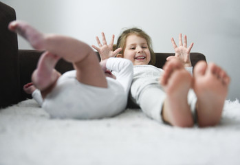 Little girl is smiling laying with her baby brother. Photo with soft focus on a girl.