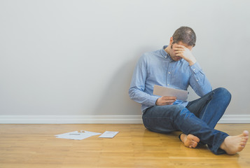 Very upset man sitting at the floor with bills.