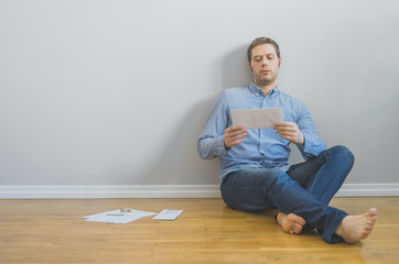 Tired man sitting at the floor with bills.
