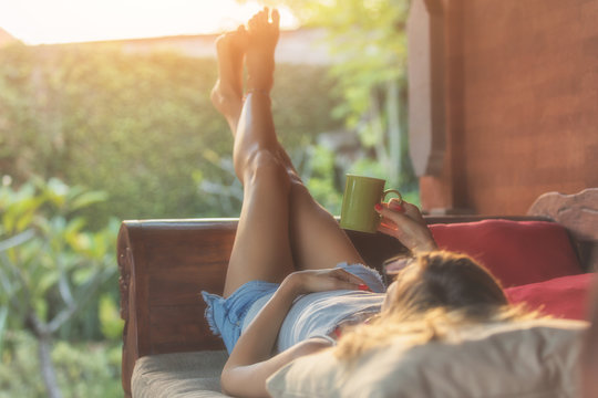 Girl enjoying morning coffee on the porch.