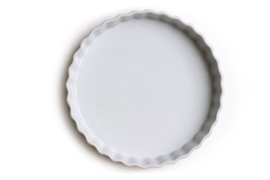 Empty ceramic tart or pie dish, on white background; with copy space