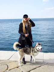 young sexy blonde sunny girl in black cap is standing fashion and posing with cute husky on the blue sea background