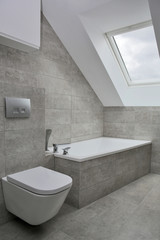 Furnished bathroom with white furniture, tiles in grey