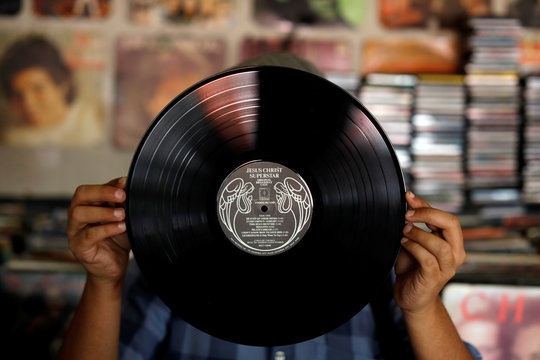 "A man shows a vinyl record at ""El Pollo Musical"" (The Musical Chicken) record store in San Salvador"