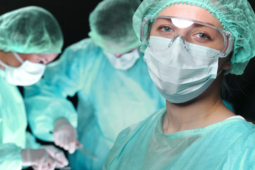 Closeup of surgeons performing operation. Focus on female doctor. Medicine, surgery and emergency help concepts
