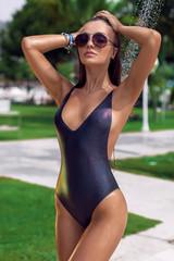 Gorgeous wet girl in a black bathing suit enjoying the sun