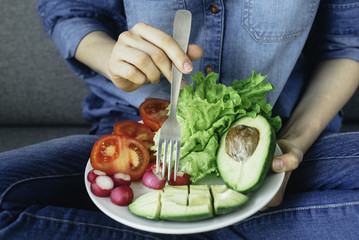 young woman eating fresh vegetables at home. Vegan eating avocado, salad, radish and tomatos