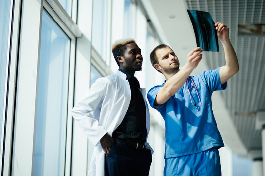 healthcare, medical and radiology concept - two mixed race doctors looking at x-ray in modern hospital