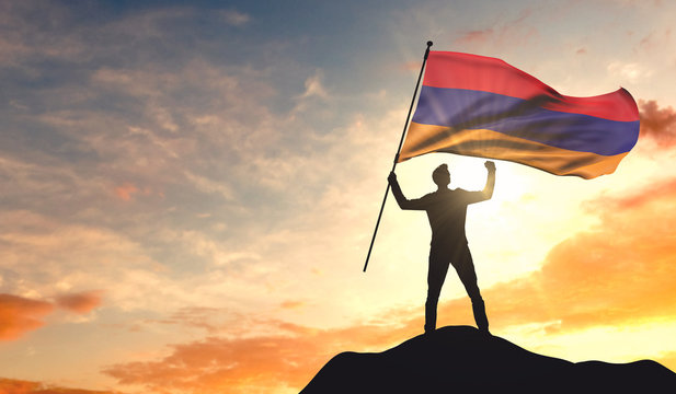 Armenia flag being waved by a man celebrating success at the top of a mountain. 3D Rendering