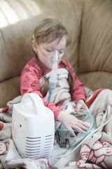 Little girl treats a runny nose using a nebulizer, treatment at home
