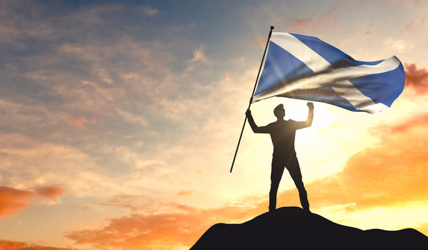 Scotland flag being waved by a man celebrating success at the top of a mountain. 3D Rendering