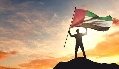 United Arab Emirates flag being waved by a man celebrating success at the top of a mountain. 3D Rendering